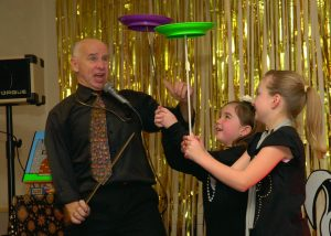 Showing Mr Giggles Magician and children spinning plates at a magic party